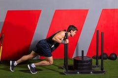 Uomo di spinta della slitta che spinge esercizio di allenamento dei pesi Immagini Stock