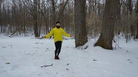 Uomo di sport in cappotto giallo che salta con la corda nella foresta di inverno con spazio libero video d archivio