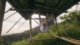 Uomo di sport che appende sulla barra trasversale di legno che fa l'ABS che si prepara sul paesaggio tropicale della natura ABS e stock footage
