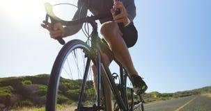 Uomo di Triathlete che cicla un giorno soleggiato archivi video