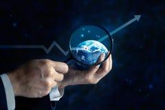 Uomo di Usiness che guarda un grafico commerciale verso l'alto sul globo e sulle stelle dalla lente d'ingrandimento in mani, conc Fotografia Stock