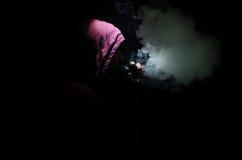 Uomo di Vaping che tiene un MOD Una nuvola del vapore Priorità bassa nera Vaping una sigaretta elettronica con molto fumo Immagine Stock Libera da Diritti
