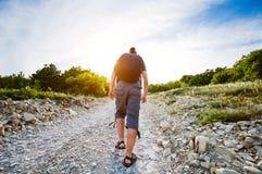 Uomo di viaggio che aumenta su per la strada rocciosa Fotografia Stock Libera da Diritti