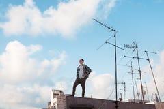 Uomo di viaggio che sta sul tetto, sorridente e guardante lontano con il cielo blu luminoso e nuvole ed antenne bianche fotografie stock