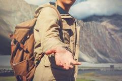 Uomo di viaggio dei giovani che dà una mano nel paesaggio all'aperto della montagna Fotografie Stock Libere da Diritti