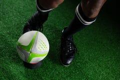 Uomo di vista dell'angolo alto che dà dei calci alla palla di rugby Immagine Stock Libera da Diritti