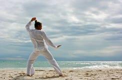 Uomo di Wushu sulla spiaggia Fotografia Stock Libera da Diritti