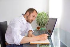 Uomo dietro il computer portatile sul lavoro fotografia stock libera da diritti