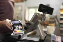 Uomo dietro il contatore ad un terminale d'offerta della carta di credito del caffè fotografia stock libera da diritti