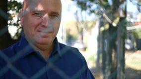Uomo dietro il recinto Look di protezione alla macchina fotografica ed il sorriso promettente stock footage