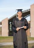 Uomo in diploma della tenuta dell'abito di graduazione sull'istituto universitario Fotografie Stock