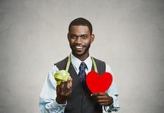 Uomo, dirigente aziendale che tiene mela verde, cuore rosso Immagine Stock Libera da Diritti