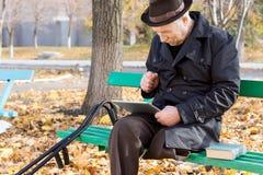 Uomo disabile anziano che legge un libro elettronico Immagini Stock