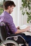 Uomo disabile capace che legge un libro fotografie stock