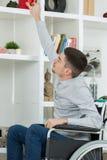 Uomo disabile capace che sceglie libro dallo scaffale fotografia stock