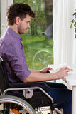 Uomo disabile a casa che legge un libro Fotografie Stock