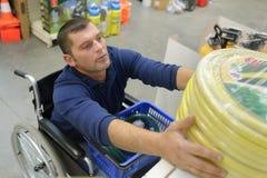 Uomo disabile che lotta per raggiungere tubo flessibile al deposito di giardinaggio immagine stock