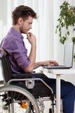 Uomo disabile che per mezzo di un computer portatile Fotografia Stock Libera da Diritti