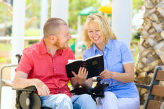 Uomo disabile con il suo fiilng della moglie felice mentre leggendo bibbia santa Fotografia Stock Libera da Diritti
