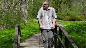 Uomo disabile con le grucce che cammina sul ponte archivi video