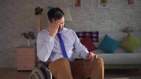 Uomo disabile del ritratto in una sedia a rotelle è triste e solo stock footage