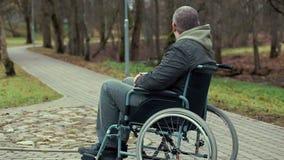 Uomo disabile nell'assistenza aspettante della sedia a rotelle sul percorso nel parco stock footage
