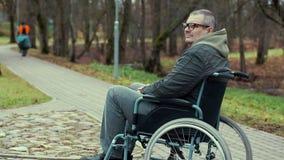Uomo disabile in sedia a rotelle che aspetta sul percorso nel parco archivi video