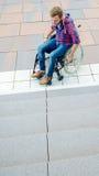 Uomo disabile in sedia a rotelle davanti alle scale Immagini Stock