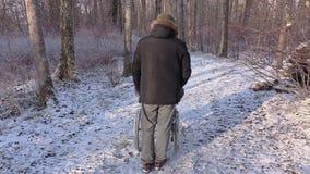 Uomo disabile sulla sedia a rotelle con l'addetto nel parco video d archivio
