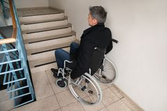 Uomo disabile sulla sedia a rotelle davanti alla scala Immagine Stock