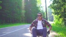Uomo disabile in una sedia a rotelle con un viaggio dello zaino archivi video