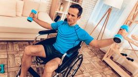 Uomo disattivato in sedia a rotelle con le teste di legno in mani immagini stock libere da diritti