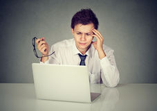 Uomo disperato degli impiegati con funzionamento di vetro sul computer portatile Fotografia Stock Libera da Diritti