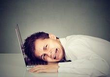 Uomo disperato di affari con la testa sulla tastiera del computer portatile Immagine Stock
