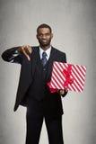 Uomo dispiaciuto che dà a pollici giù al regalo ha ricevuto Fotografie Stock Libere da Diritti