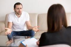 Uomo disturbato arrabbiato che sporge querela allo psicoterapeuta femminile, talkin Fotografia Stock