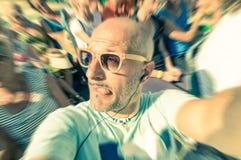 Uomo divertente calvo che prende un selfie nella folla con la lingua fuori Immagine Stock