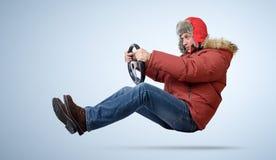Uomo divertente in cappuccio che conduce un'automobile nell'inverno immagini stock