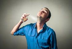 Uomo divertente che applica profumo Fotografia Stock Libera da Diritti