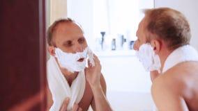 Uomo divertente che firma durante la rasatura di mattina stock footage