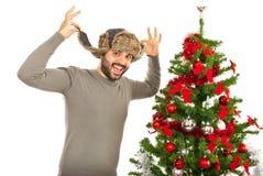 Uomo divertente con il cappello di pelliccia vicino all'albero di natale Immagine Stock
