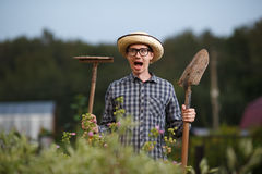 Uomo divertente dell'agricoltore con la pala ed il rastrello a bocca aperta Immagini Stock Libere da Diritti