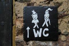 Uomo divertente di simboli della toilette del wc che prova ad esaminare donna nella toilette immagine stock libera da diritti