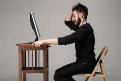 Uomo divertente e pazzo che per mezzo di un computer Immagini Stock