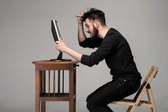Uomo divertente e pazzo che per mezzo di un computer Immagine Stock Libera da Diritti
