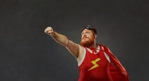 Uomo divertente grasso in un costume del supereroe fotografia stock libera da diritti