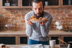 Uomo dolce casalingo del forno che odora le pasticcerie fresche immagine stock