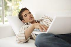 Uomo domestico di tecnologia sul sofà con il computer portatile Fotografia Stock Libera da Diritti
