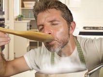 Uomo domestico felice ed attraente del cuoco in grembiule che sorride stufato avente un sapore allegro e affascinante con il cucc immagine stock libera da diritti