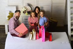 Uomo, donna e bambini adorabili con i regali a casa fotografia stock
